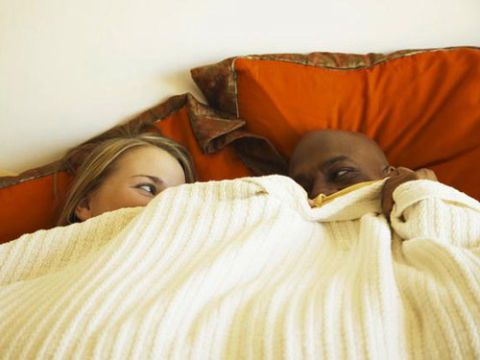 hombre and woman ducking under covers in bed