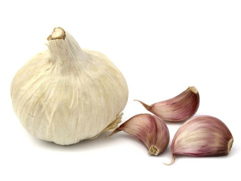 बल्ब of garlic with three loose cloves on white background