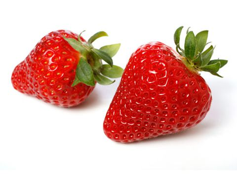 क्लोज़ अप of two ripe red strawberries on white background