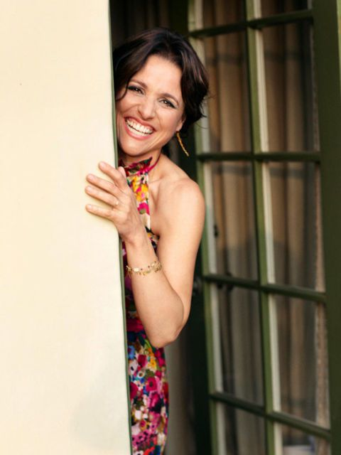 színésznő julia louis-dreyfus peeking behind a door and laughing