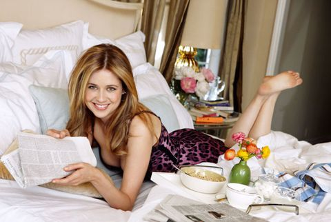 Jenna fischer on bed with cereal and newspaper