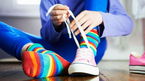 Kind with rainbow socks tying shoes